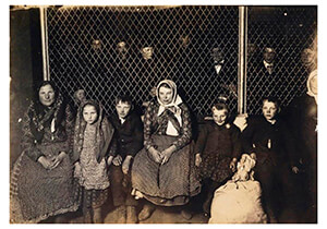 Lewis Hine(1874-1940) -Family Group At Ellis Island (With Immigrants Behind A Hurri- Postkaart
