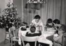 Spaarnestad Fotoarchief,  -  Hongaars gezin zit aan tafel met kerstboom en kerstklok - Postkaart -  D1176-1