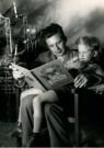 Spaarnestad Fotoarchief,  -  Vader zit naast de kerstboom in de leunstoel - Postkaart -  D1190-1