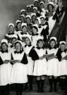 Spaarnestad Fotoarchief,  -  Weesmeisjes staan kerstliederen te zingen - Postkaart -  D1194-1
