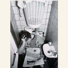 Man met krant op wc