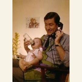 Telefonerende vader geeft baby de fles, 1961
