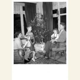 Gezin zingt kerstliedjes bij de kerstboom