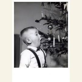 Net jongetje met kaarsje een kerstboom