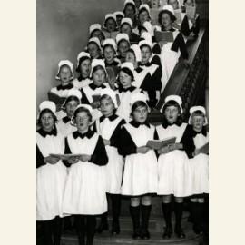 Weesmeisjes staan kerstliederen te zingen